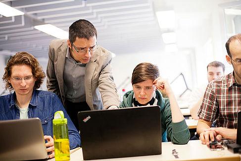 Professor erklärt Studierenden etwas am Computer